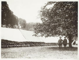 Photograph of Dr. John Stewart standing beside field hospital ward
