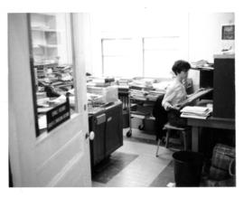 Photograph of Gloria Hardy working in the Serials Department of the 5963 College Street building