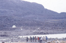Photograph of a group of people carrying a beam in Cape Dorset, Northwest Territories