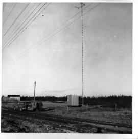 Photograph of an unidentified radio tower with two people on the ground