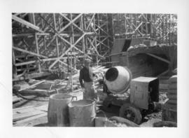 Photograph of a man with a cement mixer