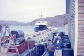 Photograph of Mrs. Sam Lyall and two children standing by a dock in Nain, Newfoundland and Labrador