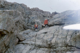 Photograph of two people standing on a rock formation in the eastern Canadian Arctic
