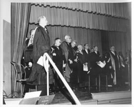 Photograph of unidentified people and Dr. A. E. Kerr in robes on stage