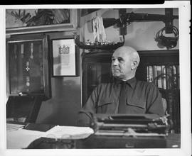Photographic negative of Thomas Head Raddall sitting at the desk in his study with a bookshelf, d...