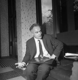Photograph of an unidentified man sitting on a bench