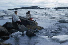 Photograph of Barbara Hinds and another woman sitting on rocks by the water in Frobisher Bay, Nor...