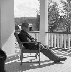 Photograph of John Drabson sitting on the verandah of the Old Men's Home in Dawson City, Yukon