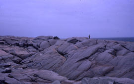 Photograph of a landscape of giant rocks by the water with an unidentified man standing on top