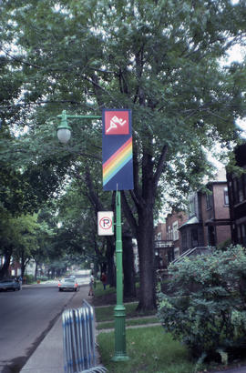Photograph of a street sign featuring a rainbow and an active person