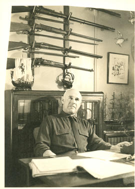 Photograph of Thomas Head Raddall sitting at his desk in his study
