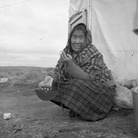 Photograph of Alacee Qingalik holding an ulu and a cigarette in Povungnituk, Quebec