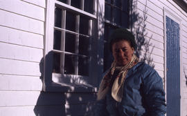 Photograph of Barbara Hinds standing by the window of a white house