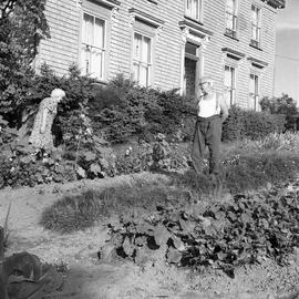 Photograph of Mr. and Mrs. Ernest Arthur Farrant standing in a garden in front of a house