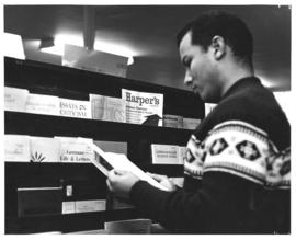 Photograph of a student reading a periodical in the Macdonald library
