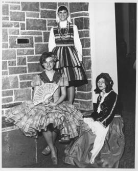 Photograph of three women in different international dress