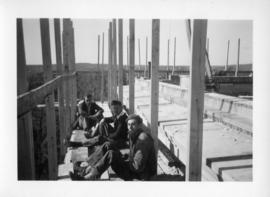 Photograph of men sitting on the Arts & Administration Building construction site