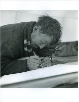 Photograph of an unidentified man drawing with a pencil