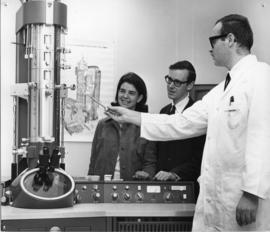 Photograph of Morley Bleviss showing an electron microscope to two attendees at an open house