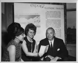 Photograph of three people examining a brochure at the 1967 World Exhibition in Montreal