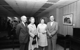 Photograph of four unidentified people at the presentation of a painting of Chester Stewart