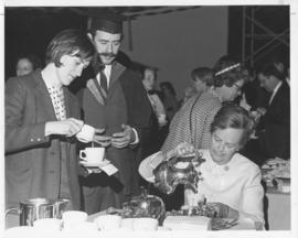 Photograph of an unidentified person serving tea at a convocation tea