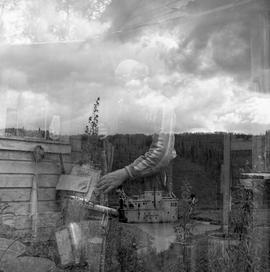 Double exposure photograph of a building and a man with a rifle