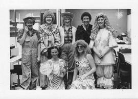 Photograph of circulation desk employees wearing costumes