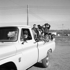 Photograph of Canon James Clarke driving pickup truck with several children in the back in Fort C...