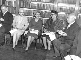 Photograph of unidentified people eating in a library