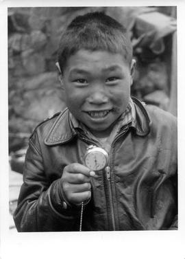 Photograph of a boy named Sapinak holding a pocket watch