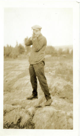 Photograph of a man holding a rifle and pretending to shoot the camera