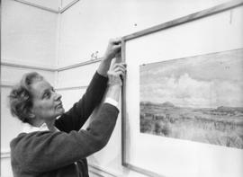 Photograph of Evelyn Holmes hanging a picture