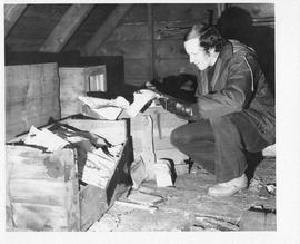 Photograph of Charles Armour looking at crates of documents