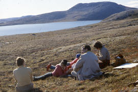 Photograph of a group of people reclining outdoors at Tellik Inlet, Northwest Territories