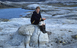 Photograph of Barbara Hinds sitting on a rock near Cape Dorset, Northwest Territories