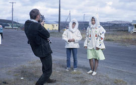 Photograph of two young women wearing white parkas and being filmed by a man