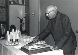 Photograph of Thomas Head Raddall cutting a cake at the first birthday of the Perkins House Museu...