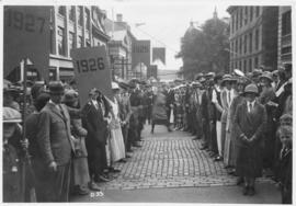 Photograph of alumni lined up on either side of a street