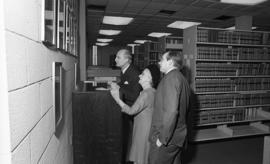 Photograph of three unidentified people in the law library