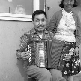 Photograph of Jimmy Koneak with his wife and an accordion in Fort Chimo, Quebec