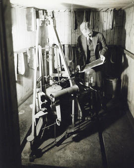 Photograph of man with large piece of equipment in the Science Building