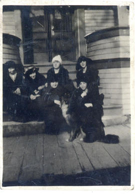 Photograph of a group of women wearing hats and posing with a dog