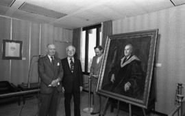 Photograph of Chester Stewart and two unidentified people with a painting