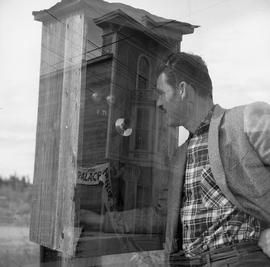 Double exposure photograph of a building and a man with a telephone