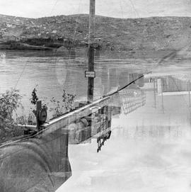 Double exposure photograph of a truck and equipment near the water near Dawson City, Yukon