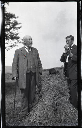 Two men in a hay field