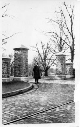 Photograph of a man standing next to the class of 1912 memorial