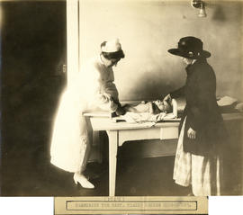 Photograph of Health Centre No. 1 nurse leaning over and measuring baby