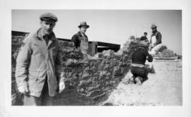 Photograph of men building a stone wall